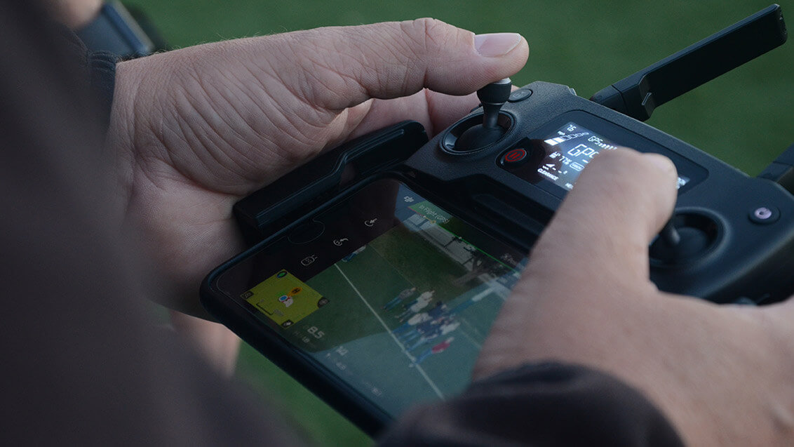 Close up of hands on drone controls.