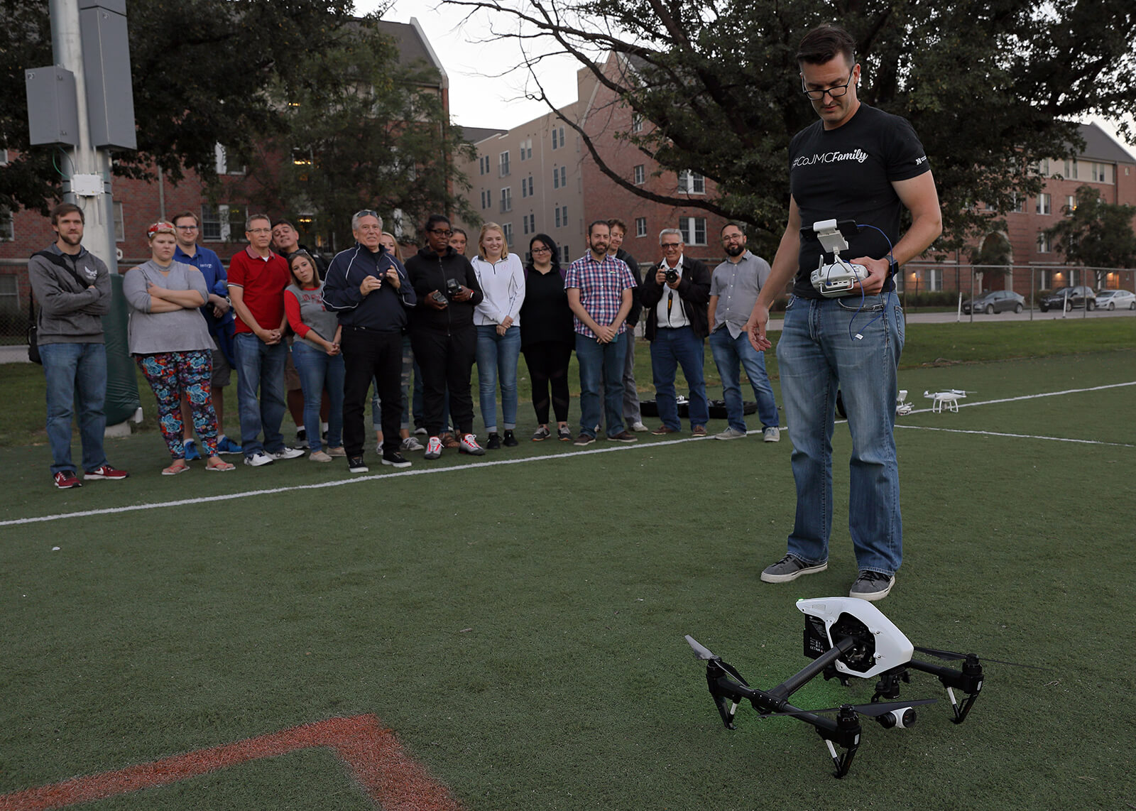 Students look on in the background as Waite look down on a drone and controls in foreground.