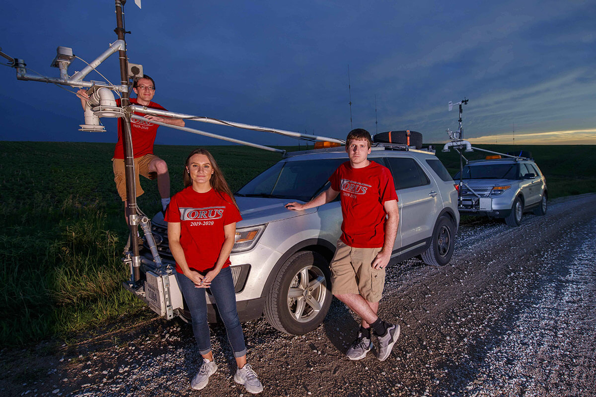 Three student members of the TORUS team posing in front of a custom outfitted chase vehicle.