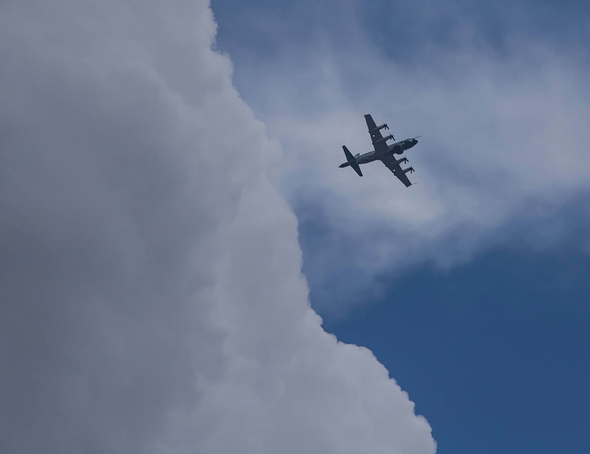 An airplane from below zooming out of a dark cloud bank.