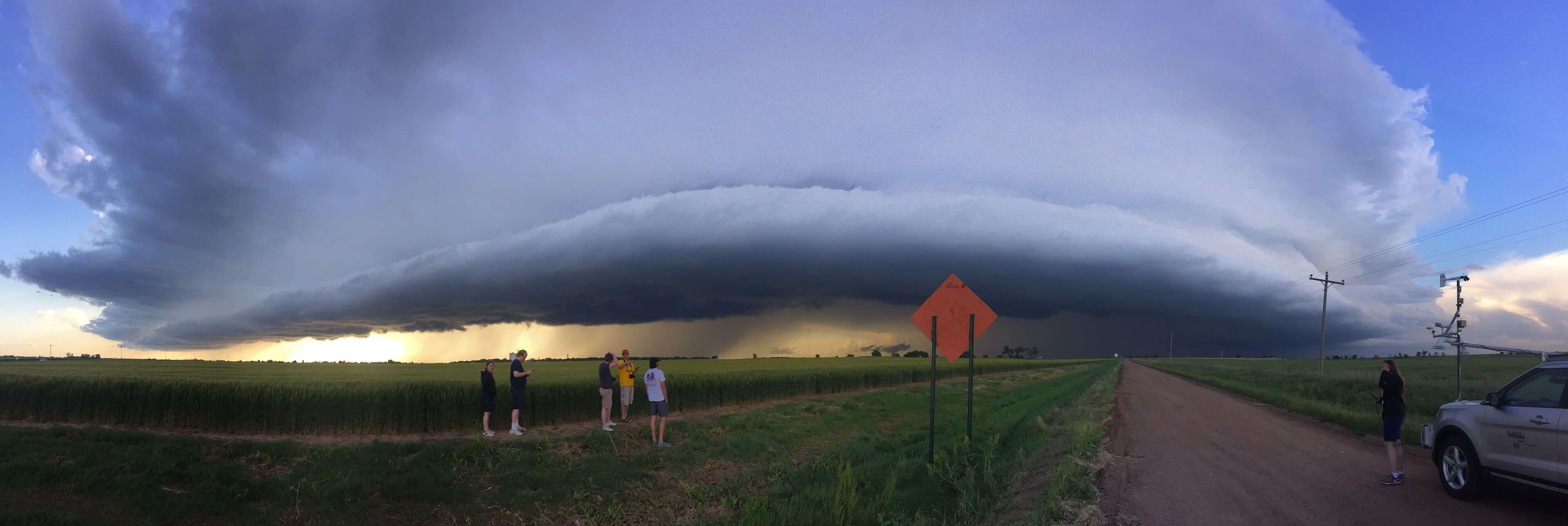 panoramic shot of storm clouds with researchers in the foreground.